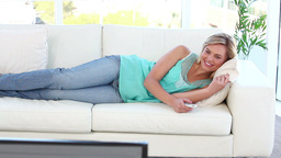 Smiling woman watching the television Footage
