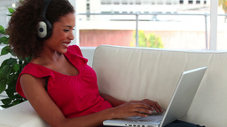 Smiling woman using a laptop while listening to mu Footage