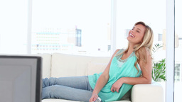 Woman laughing while watching the television Footage