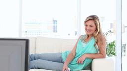 Woman laughing while watching the television Stock Video Footage