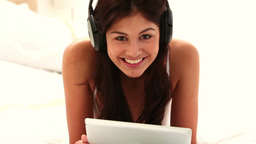 Brunette woman using a tablet pc while listening t Footage