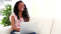 Laughing brunette woman using a laptop Stock Video Footage