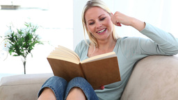 Woman reading a book on her sofa Live Action
