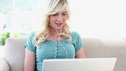 Young woman using a laptop and wearing earphones Footage