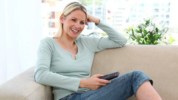 Blonde woman watching TV alone Stock Video Footage