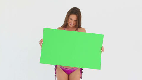 Woman in a pink bikini holding a blank poster Footage