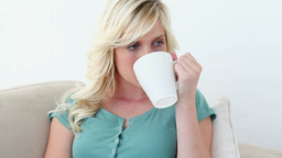 Blonde woman smells and drinks a coffee Footage