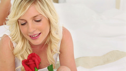 Blonde haired woman smelling a rose Stock Video Footage