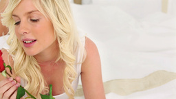 Blonde haired woman smelling a rose Footage