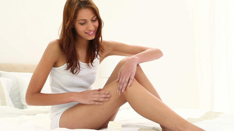Brunette haired woman applying moisturizer on her legs Footage