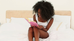 Laughing black haired woman reading a book Live Action