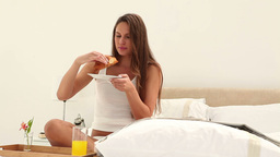Young woman eating breakfast while reading the new Footage