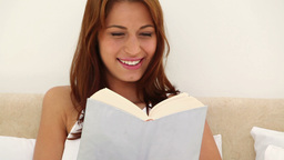 Brunette haired woman reading a novel Stock Video Footage