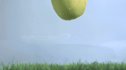 Green apple in super slow motion falling on the gr Stock Video Footage