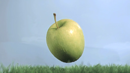 Green apple in super slow motion falling on the gr Footage