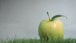 Apple in super slow motion placed on the grass Footage