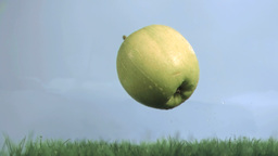 Wet apple in super slow motion falling on the gras Footage