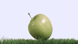 Green apple falling in super slow motion on the la Stock Video Footage