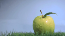 Apple in super slow motion being wet on the grass Stock Video Footage