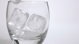 Ice cubes in super slow motion put in a tumbler Live Action
