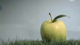 Apple in super slow motion put on the lawn Footage