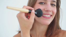 Smiling woman applying foundation on her face Stock Video Footage