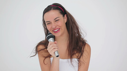 Happy brunette woman with a microphone is singing Footage