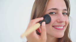 Smiling brunette woman using a powder brush Footage