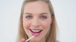 Smiling blonde woman applying lip gloss on her lip Stock Video Footage