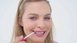 Smiling blonde woman applying lip gloss on her lip Footage