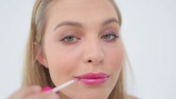 Blonde woman applying lip gloss on her lips Footage