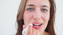 Cheerful woman using lip balm on her lips Footage
