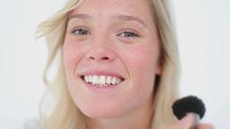 Woman applying foundation with a powder brush Footage