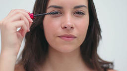 Happy brunette applying mascara on her eyelashes Footage