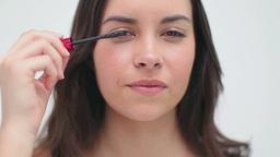 Happy brunette applying mascara on her eyelashes Stock Video Footage