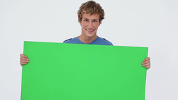 Smiling brunette man holding a blank poster Stock Video Footage
