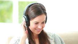 Smiling brunette woman listening to music with hea Footage