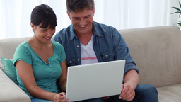 Happy couple looking at a laptop together Footage