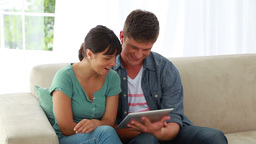 Smiling couple using an ebook together Footage