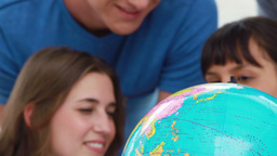 Smiling students looking at the world on a globe Footage