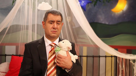 Sad man sitting inside of playpan with toy lamb Footage