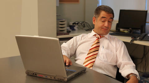Tired businessman using laptop in office Footage