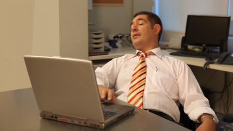 Tired businessman using laptop in office Stock Video Footage