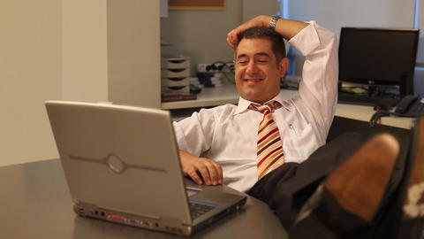 Relaxed businessman working on laptop in office Stock Video Footage