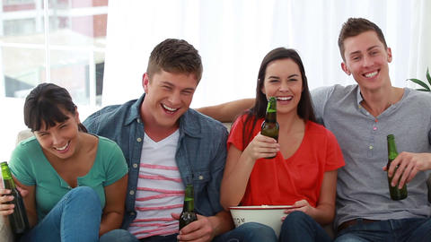 Two couples watching the television together Stock Video Footage