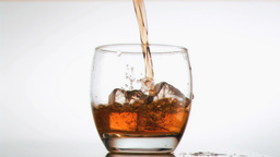 Whiskey flowing in super slow motion in a glass Stock Video Footage