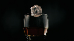 Ice cube rolling in super slow motion into a glass Footage