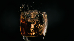 Ice cube falling in super slow motion in whiskey Footage