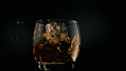 Ice cube falling in super slow motion in whiskey Stock Video Footage