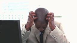 Black man in suit rubbing his head Stock Video Footage